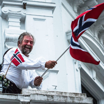 Jovial Man Hoisting the National Flag at the Balcony of his own House, in the City of Bergen