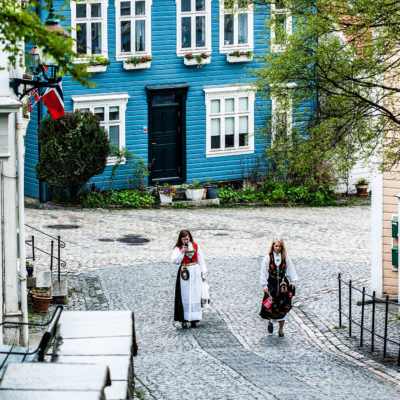 Two Damsels Wearing the Traditional Costume Go Up the Sydneskleiven, Street with Classic Wood Houses in the Ancient Quarter of Sydnes in Bergen